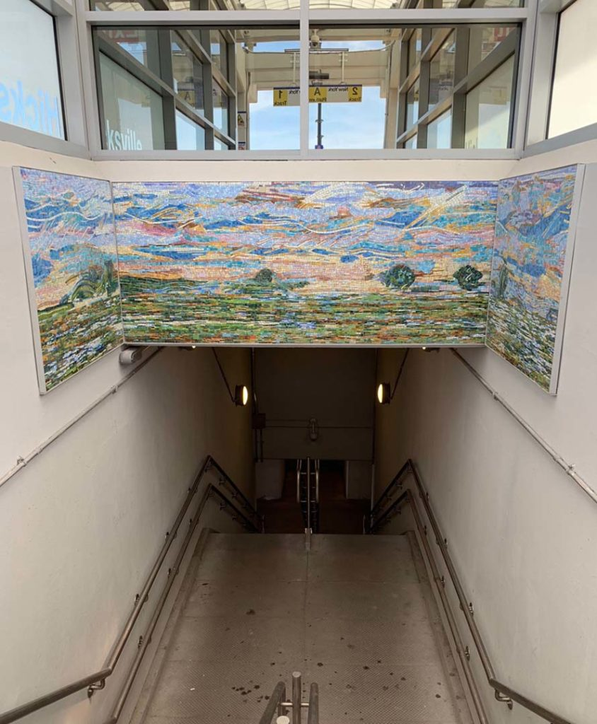 Hicksville Station, Westbound Staircase, Sunrise, Hempstead Plain, glass mosaic, installed 2019, commissioned by MTA Arts & Design. Photo, Stephen Miotto.
